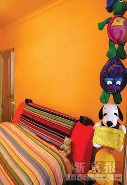 橙色的卧室,可爱的娃娃爬上窗帘架,艳丽的床单烘托出温暖的气息,这是