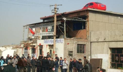 山东东营,东城沙营村六旬军属老人纪庆玉在自家门前手举五星红旗.